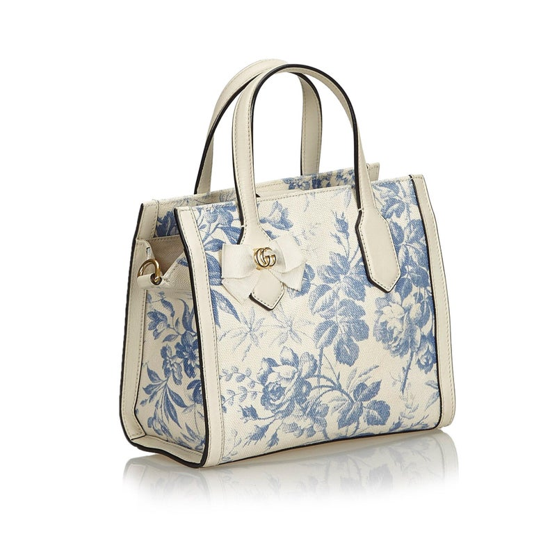 This satchel features a floral canvas body with leather trim, flat leather handles, a flat shoulder strap, an open top with a magnetic closure, and interior slip pockets. It carries as B+ condition rating.  Inclusions:  This item does not come with