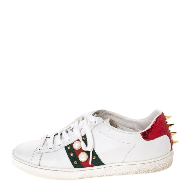 Stacked with signature details, this Gucci pair is rendered in leather and is designed in a low-cut style with lace-up vamps. They have been fashioned with the iconic web stripes and a mix of spikes, studs and faux pearls. Complete with red and