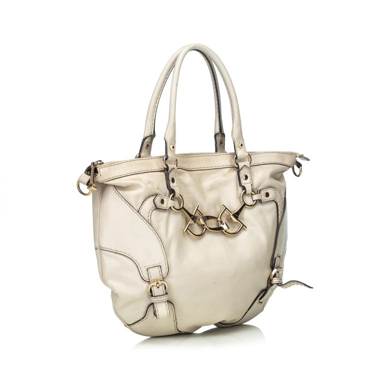 This satchel features a leather body with silver-tone horsebit details, rolled leather handles, a detachable flat leather strap, a top zip closure, and interior pockets. It carries as B condition rating.  Inclusions:  This item does not come with