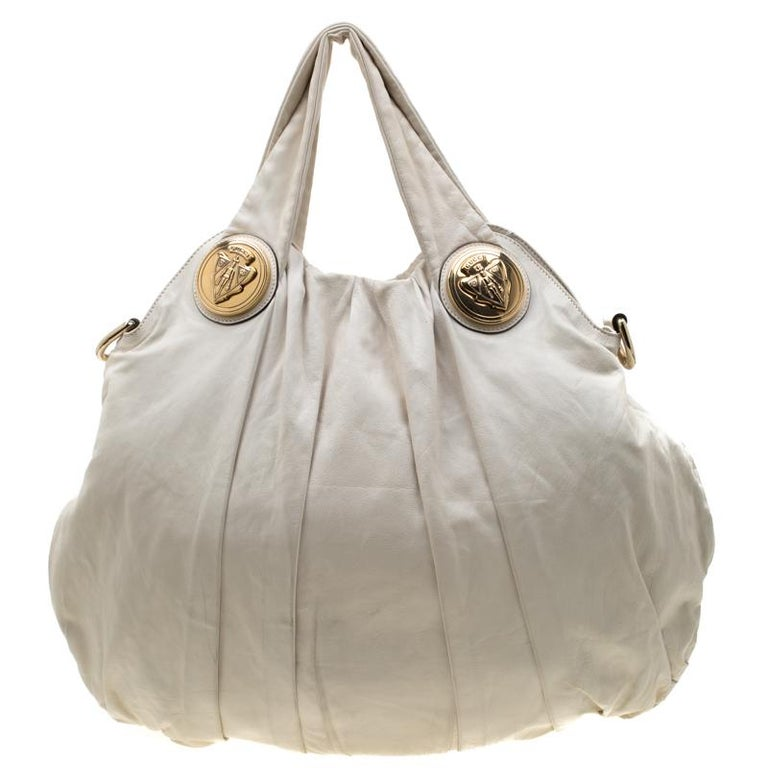 This Gucci hobo is built for everyday use. Crafted from leather, it has a white exterior and two handles for you to easily parade it. The fabric insides are sized well and the hobo is complete with the signature emblems.  Includes: The Luxury Closet