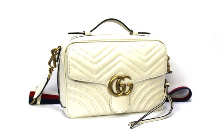 Gucci bag Marmont line made of white leather with golden hardware. Equipped with top handle and removable web band shoulder strap. Zip closure, internally large enough. Equipped with front pocket with flap. The bag is in excellent condition.