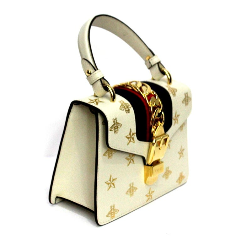 Fantastic Gucci Sylvie Bee Star line bag in its mini size Made of white leather with bees print and gold stars. Gold hardware, enriched by the classic red and blue Web tape. Closure with hook, internally large for the essentials, Equipped with a