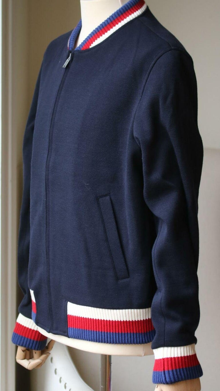 Displayed on a jersey wool bomber jacket. Blue stitch jersey wool. Webbing trim. Cotton lining. Knit rib trims. Front slash pockets. Interior pockets. Front zip closure. 80% Wool, 20% polyamide.  Size: IT 52 (XLarge, Chest 106 cm)  Condition: As new