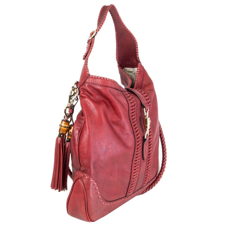 authentic Gucci x Green Carpet Challenge 'New Jackie Large' hobo in burgundy distressed calfskin featuring light gold-tone hardware. Lined in off-white canvas with one zipper pocket against the back and two small open pockets against the front.