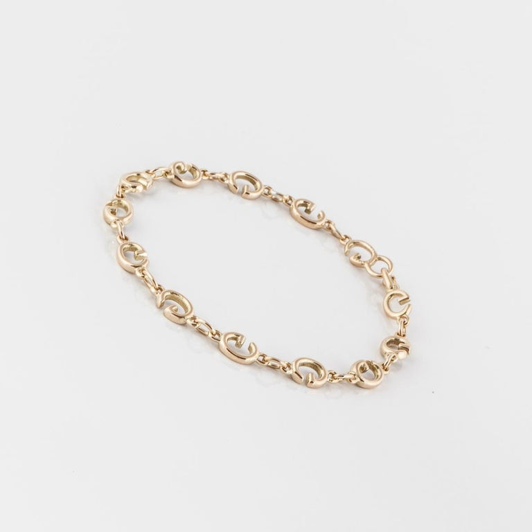 18K yellow gold bracelet by Gucci.  The links are the letter