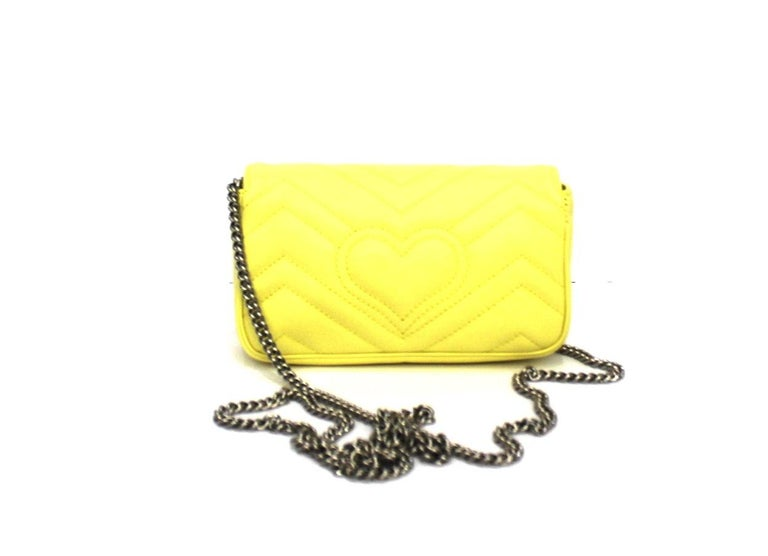 Gucci Marmont line mini bag made of soft yellow leather with silver hardware.  Equipped with chain shoulder strap. Button closure, internally not very large.  Like new condition, with its original dust bag.