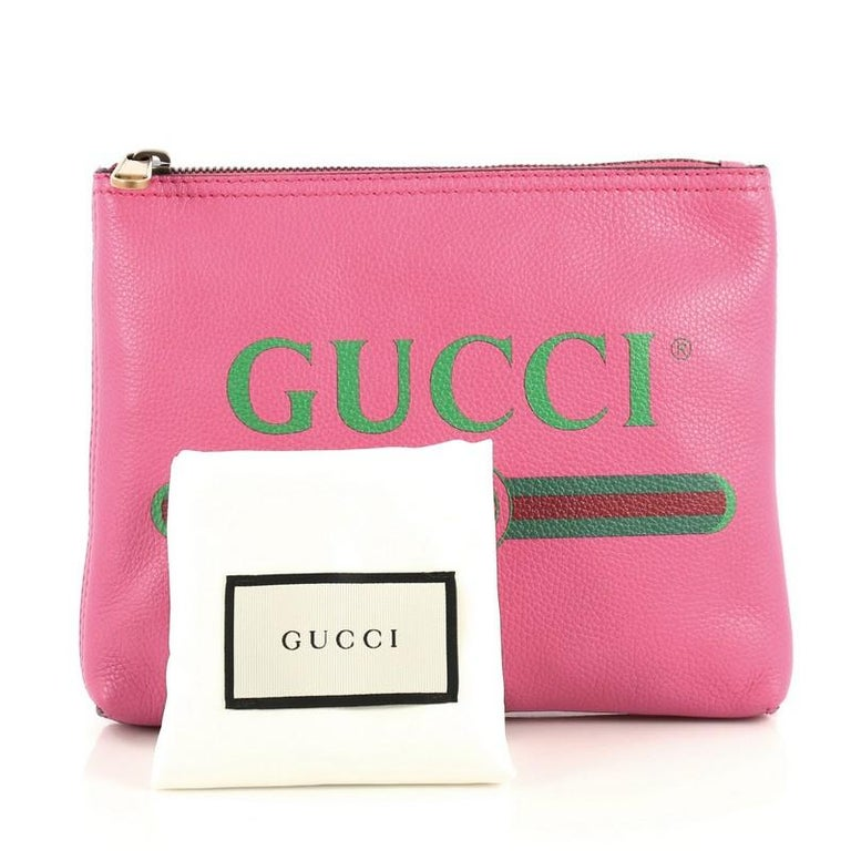 This Gucci Zipped Pouch Printed Leather Small, crafted from pink printed leather, features Gucci vintage logo print and aged gold-tone hardware. Its zip closure opens to a pink suede interior.  Estimated Retail Price: $875 Condition: Great. Minor