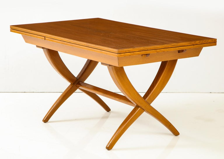 Handcrafted extension table of boldly grained oak with chamfered edges and inset leaves by Florentine artisan and designer Guglielmo Pecorini, produced in Italy circa 1950 and purchased by the previous owner from Lord & Taylor in 1951. The graceful,