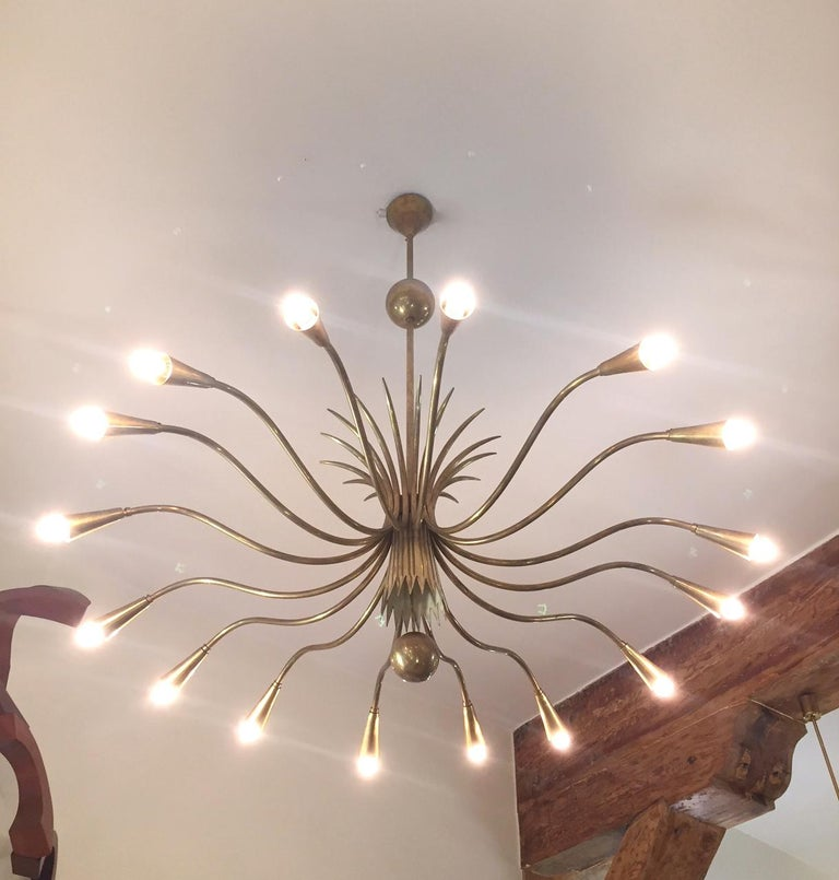 A sixteen-arm brass chandelier designed attributed to G.Ulrich in the 1940s and possibly made bi Strada Milano. Original elements, including canopy. Wired for US function boxes.