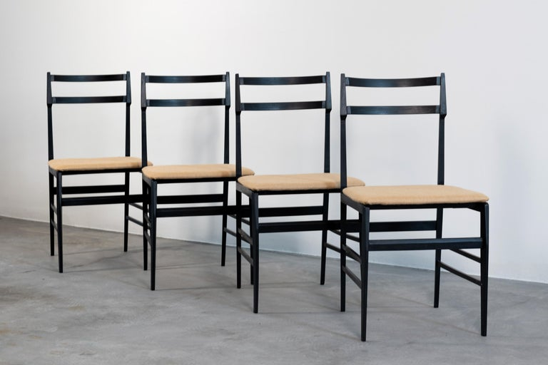 Four dining chairs by Guglielmo Ulrich (attrib.), with ebonized wood structure covered with fabric, produced by Saffa, in 1960s.  Measurements: 83 x 41 x 50 cm (each)  Guglielmo Ulrich was an Italian architect. He was a student of 'Scuola