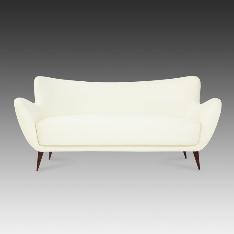 Guglielmo for I.S.A. Bergamo elegant and sculptural 'Perla' sofa with slightly curved back and gently outstretched arms ending in signature sharply tapered walnut legs, Italy, 1950s.  Fully restored and newly reupholstered in off-white cotton linen