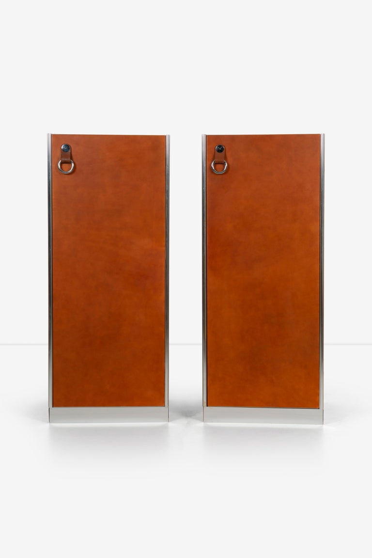 Guido Faleschini for Mariani Pace collection, pair of cabinets, featuring Leather door fronts with chrome rings which hang on a leather strap. Doors open to reveal 3 drawer cabinets, also can be removed. Track for clothes hangers pictured. Chromed