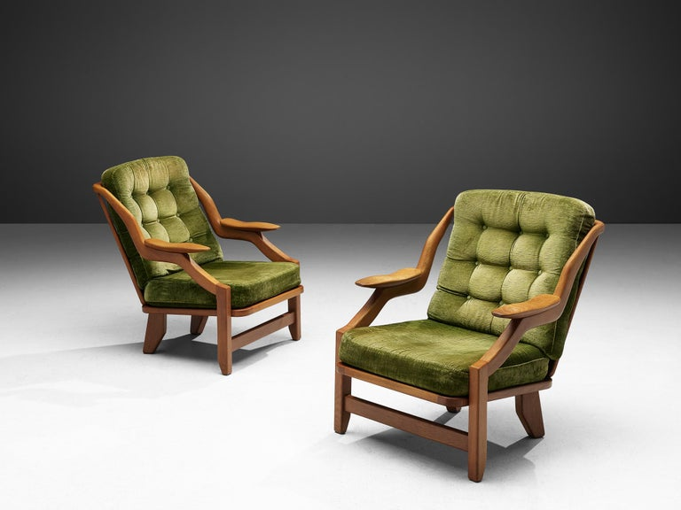 Guillerme & Chambron, set of lounge chairs in green velvet upholstery and oak, France 1950s.  This French designer duo is known for their extreme high quality solid oak furniture, from which this set is another great example. These chairs have a