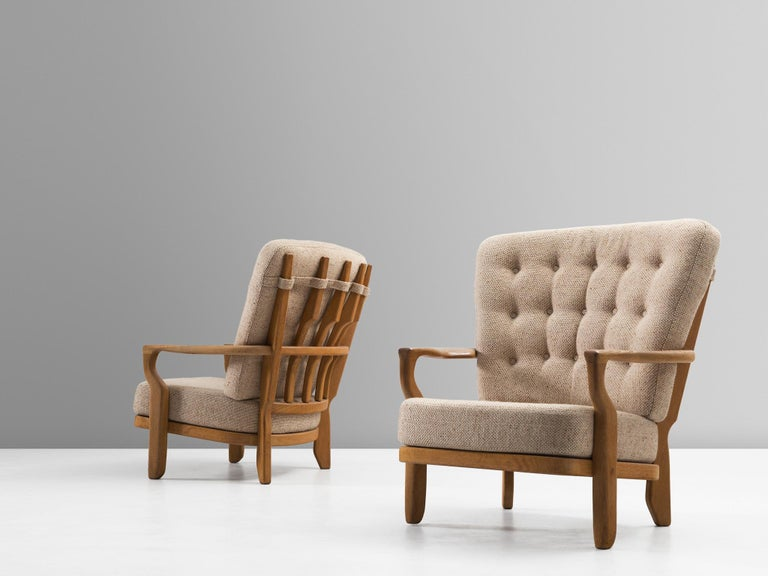 Guillerme et Chambron, lounge chair, in oak and fabric, France, 1960s.   Extraordinary Guillerme and Chambron armchair, in solid oak with the typical characteristic decorative details at the back and capricious shaped legs. Very comfortable, great