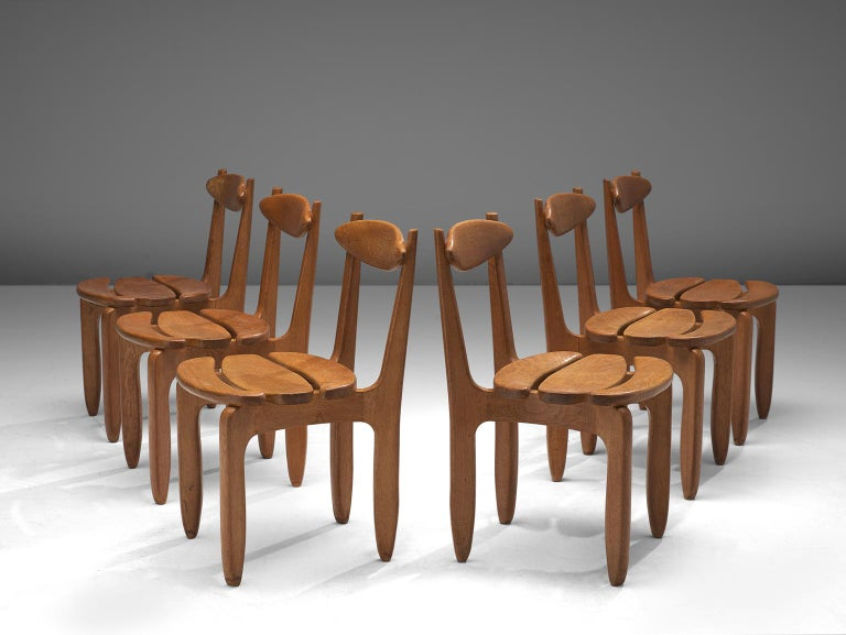 Guillerme et Chambron, set of 6 dining chairs, in oak, France, 1960s.   Set of 6 elegant and robust dining chairs in solid oak by Guillerme and Chambron. These chairs show the characteristic frame of this French designer duo, well-crafted, solid