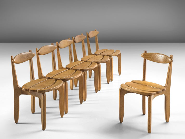Set of six dining chairs, in oak, by Guillerme & Chambron, France, 1960s.  Set of six elegant dining chairs in solid oak by Guillerme and Chambron. These chairs show the characteristic frame of this French designer duo. Tapered legs and a