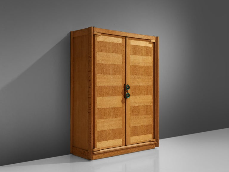 Guillerme et Chambron, armoire, oak, France, 1960s.  This case piece is designed by Guillerme and Chambron and features geometric oak inlays, which is characteristic for the French duo. The armoire is equipped with colorful, ceramic handles. The
