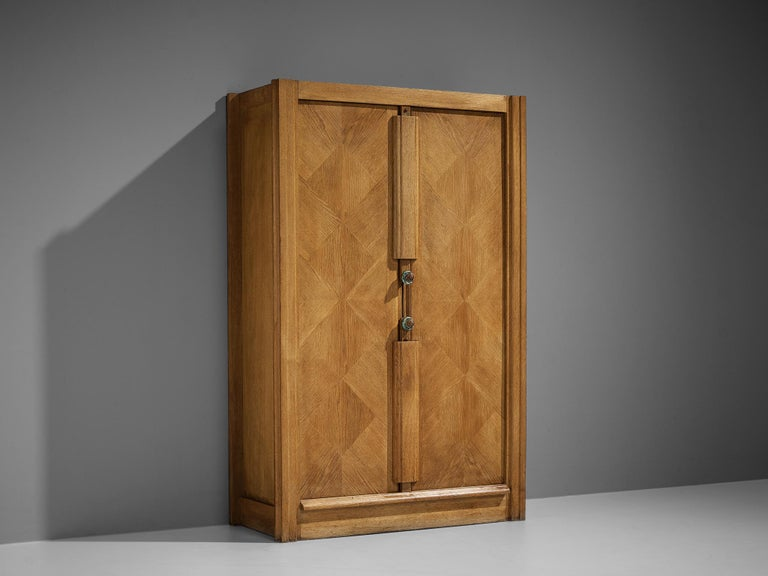 Guillerme et Chambron, cabinet, oak, ceramics, France, 1960s  This case piece is designed by Guillerme and Chambron and features geometric oak inlays, which is characteristic for the French designer duo. The center is accentuated with vertical