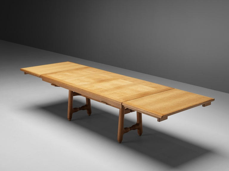 Guillerme et Chambron, dining table, oak, France, 1960s  Extendable dining table with decorative base by Guillerme et Chambron. This table holds a rectangular top with beautiful inlayed woodwork. The extension leaves make the table highly
