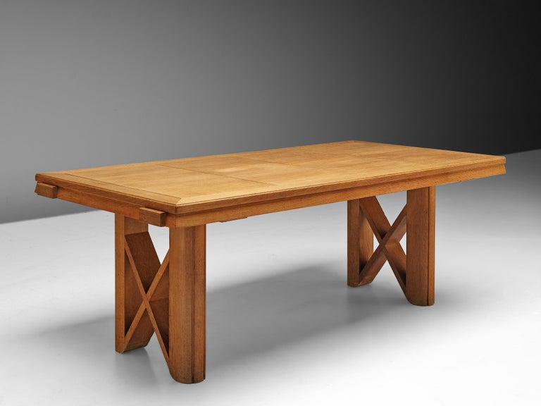 Guillerme et Chambron, extendable dining table, oak, France, 1960s  This extendable dining table is designed by French designer duo Jacques Chambron and Robert Guillerme.The legs of the table are stout and rigid with a cross section for extra
