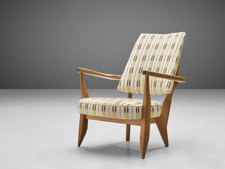 Guillerme et Chambron, easy chair, patterned fabric, oak, France, 1950s   This sculptural easy chair by Guillerme et Chambron is very well executed and made out of solid, carved oak. The comfortable armchair features an interesting open