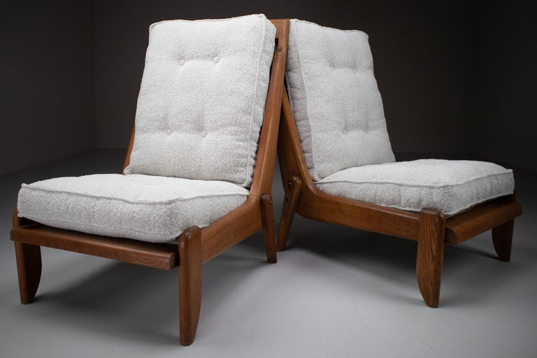 Guillerme & Chambron, pair of two lounge chairs in solid blond oak and reupholstered in bouclé fabric.   Pair of two original midcentury lounge chairs manufactured and designed by Guillerme & Chambron in France, 1950s. Made of solid blond oak and