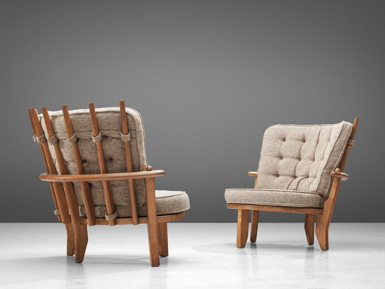Guillerme et Chambron, pair of lounge chairs, oak, beige upholstery, France, 1950s.  This set of two lounge chairs or loveseats have a classic Guillerme & Chambron style. It is bulky but beautifully made, with attention to detail and comfort.