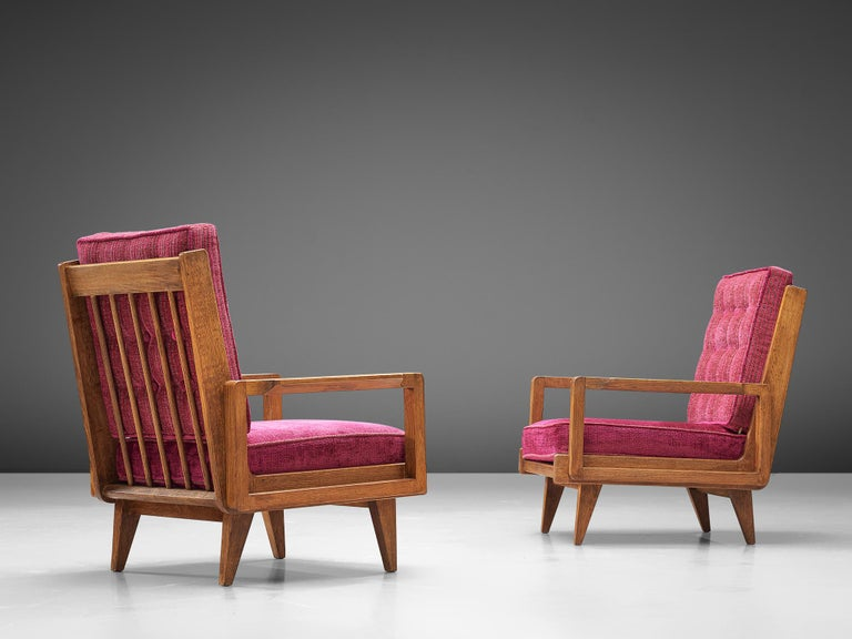 Guillerme et Chambron, pair of easy chairs, pink fabric, oak, France, 1950s  A sculptural pair of easy chairs by Guillerme and Chambron that is very well executed and made out of solid, carved oak. These armchairs feature an interesting open