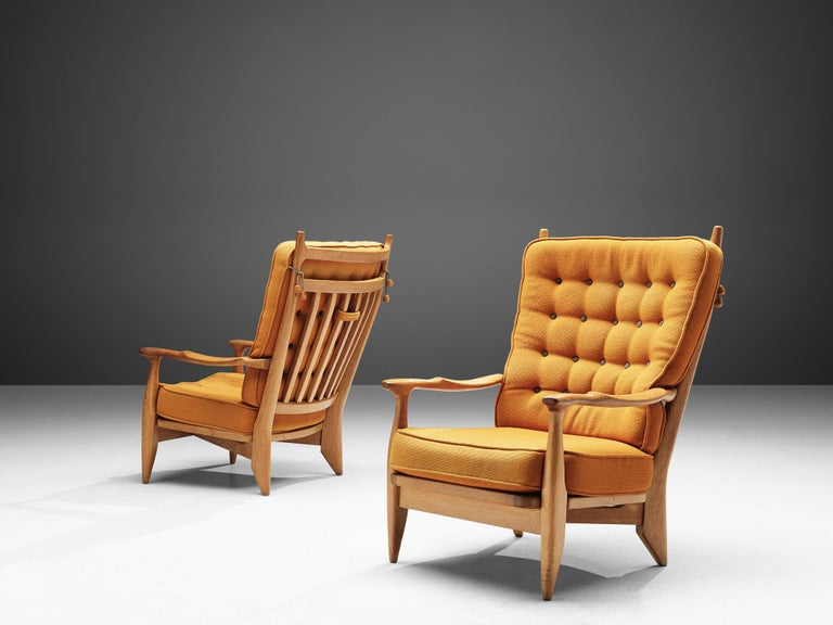Guillerme et Chambron, set of two lounge chairs oak, yellow upholstery, oak, France, 1960s.   Guillerme and Chambron are known for their high quality solid oak furniture, of which these two lounge chairs are another great example. These chairs