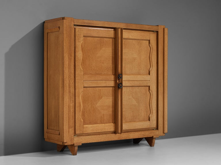 Guillerme et Chambron for Votre Maison, 'Raphael' cabinet, oak, brass, ceramics, France, 1960s  This cabinet is designed by Guillerme et Chambron and features geometric inlays in the doors. The cabinet offers plenty of storage with four shelves.