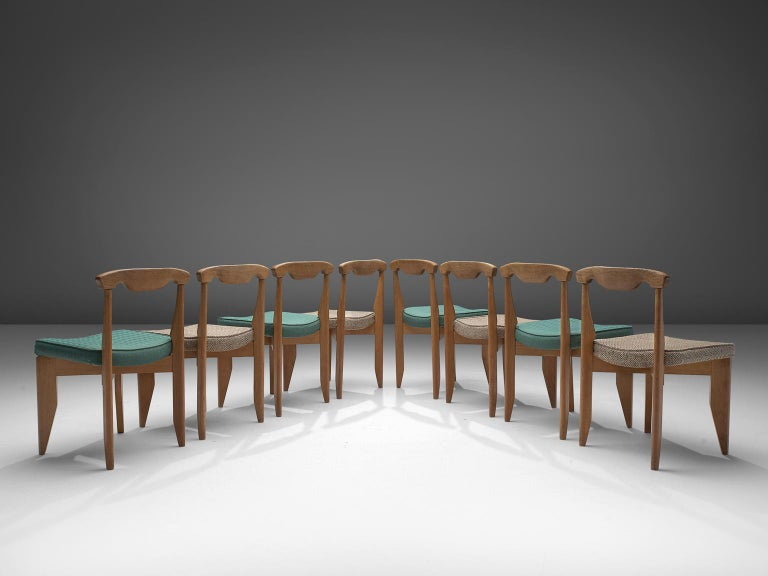Guillerme et Chambron, set of 8 dining chairs, oak, beige and green fabric, France, 1960s  These distinctive chairs in beautifully patinated oak is by the French designer duo Jacques Chambron (1914-2001) and Robert Guillerme (1913-1990). The