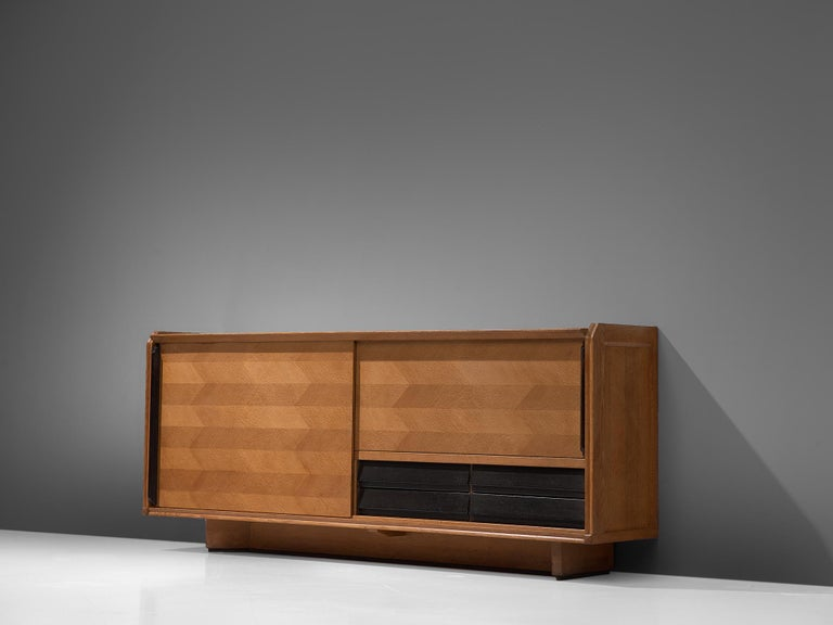 Guillerme et Chambron for Votre Maison, credenza, oak, France, 1960s  Elegant sideboard designed by the French designer duo Guillerme and Chambron. The sideboard is characterized by the horizontal oakwood inlay patterns. The oak doors feature a