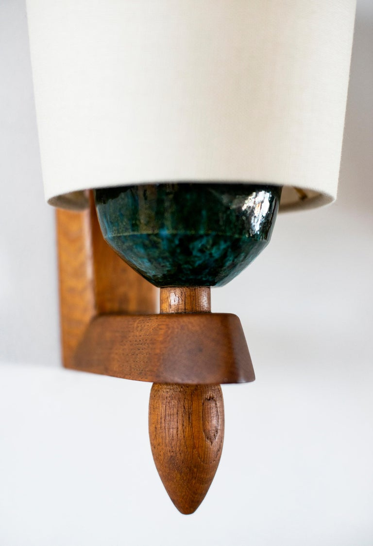 Handsome pair of French wall sconces in cerused oak by Guillerme et Chambron. Beautiful wood with new silk shade which rests on a turquoise ceramic socket.  Very unique design.  Newly rewired.