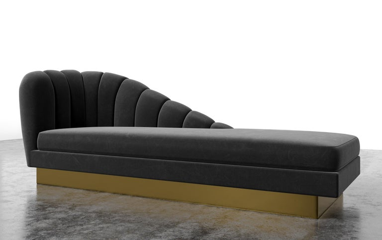The Guinevere chaise inspired by the curvature of Gaudi architecture features an asymmetrical channeled scalloped slope that meets and rests over a metal plinth base. Fully custom and made to order in California. As featured in luxury velvet