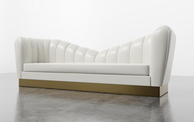 The Guinevere sofa inspired by the curvature of Gaudi architecture and features symmetrical channeled scalloped slopes that meet and rest over a metal plinth. Fully custom and made to order in California. As featured in Faux Leather/White with