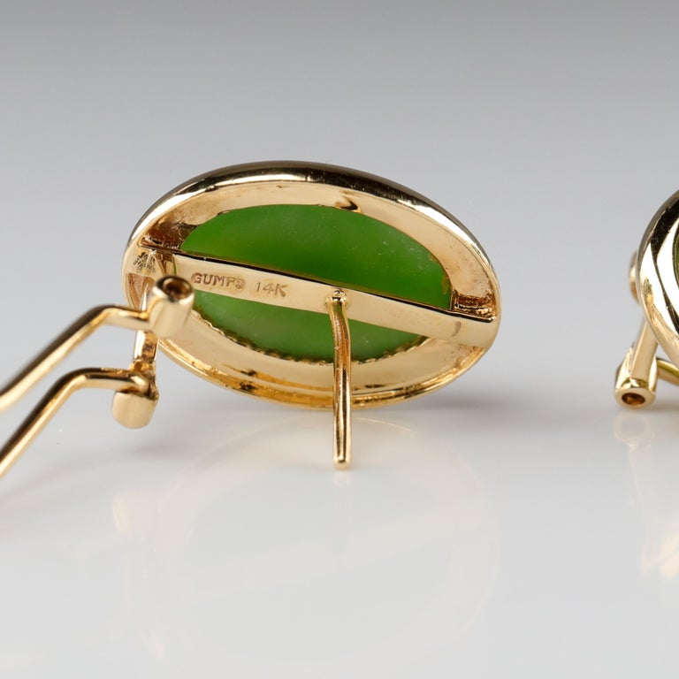 These classic circa 1990s gemmy green nephrite jade earrings were created in the 1990s by the iconic San Francisco retailer, Gump's. The name Gump's has long been associated with fine jewelry, especially natural and untreated jade. Each