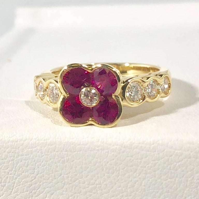 Gumuchian 18 karat Yellow gold, diamond and ruby flower cocktail ring. This designer piece by Gumuchian  is created in 18 karat yellow gold weighing 6.2 grams/ 4dwt. There are 4  round rubies  equaling 1.00 carat total weight, bright red color.