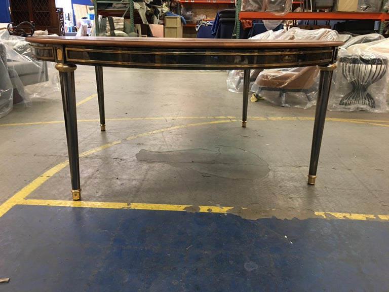 Fabulous and large scale gunmetal and brass dining table in the style of Jansen. The entire Directoire style table is constructed of polished brass, with the base of gunmetal plated brass. The legs are solid brass (not hollow cast) brass plated in