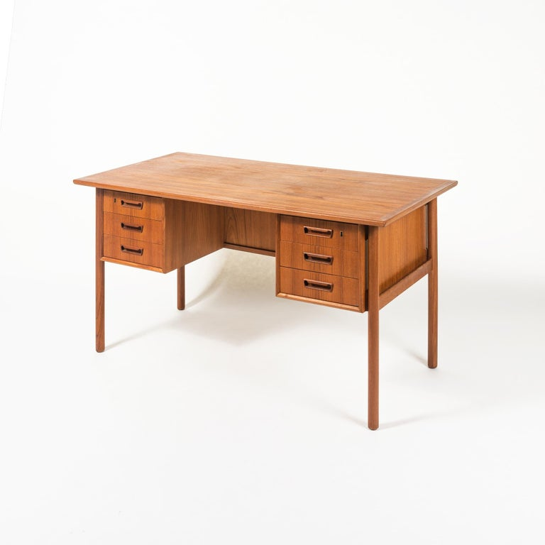 This executive desk designed by G. Nielsen Tibergaard was produced in Denmark in the 1960s. The desk is made of teak and free standing thanks to the finished back side with open storage space books . On the front there are two drawer modules with