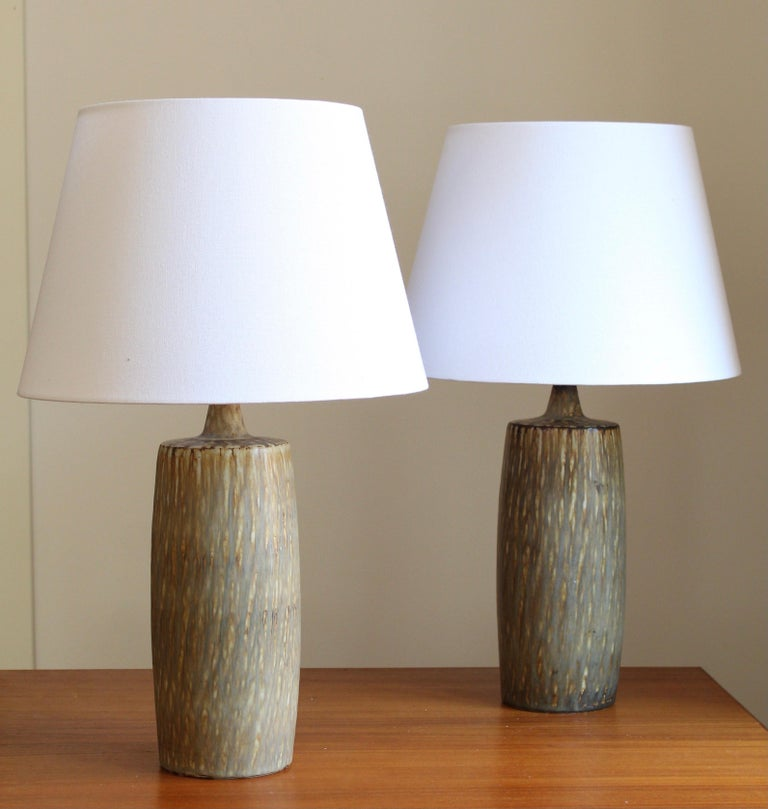 A pair of table lamps produced by Rörstrand, Sweden, 1950s. Designed by Gunnar Nylund, (Swedish, 1914-1997). Signed. Brand new lampshades. Sourced from one estate.  Nylund served as artistic director at Rörstrand, where he worked, 1931-1955. Prior