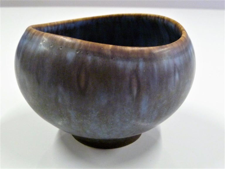 Scandinavian Modern stoneware petite pottery bowl by Gunnard Nylund for Rorstrand 1950s. Mottled glaze in blues, purple and brown, just beautiful. The vessel has no damages. The opening or mouth of bowl is elliptical rather than completely