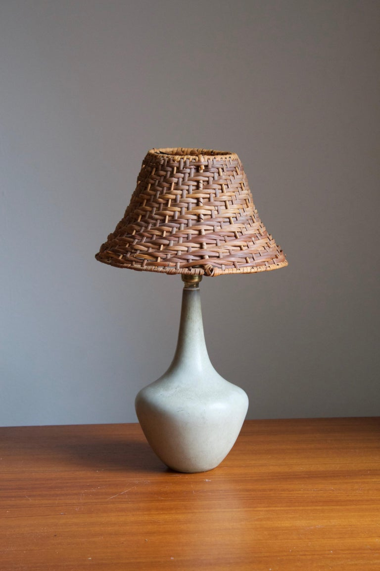 A table lamp produced by Rörstrand, Sweden, 1950s. Designed by Gunnar Nylund, (Swedish, 1914-1997). Signed.   Stated dimensions exclude lampshade, height includes socket. Upon request, a vintage rattan lampshade of the illustrated model can be