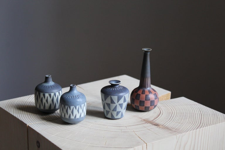 A collection of 4 small vases in stoneware and produced by Rörstrands, Sweden, 1940s. Designed and signed by Gunnar Nylund, (Swedish 1914-1997). All vases with highly artistic hand painted patterns.  Nylund served as artistic director at