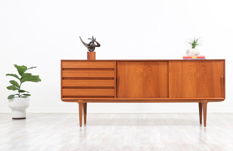Stunning modern credenza designed by Gunni Omann for family-owned company Omman Jun in Denmark circa 1960s. The low in profile and sculptural Model-18 credenza features a sturdy case with a fully finished back and warm tones that beautifully enhance