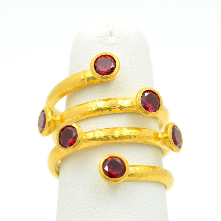 Made by Gurhan, this 24 karat yellow gold coil ring is bezel set with six round faceted topaz stones weighing approximately 1.85 carats combined. The band has a lightly hammered finish and is currently a size 6.