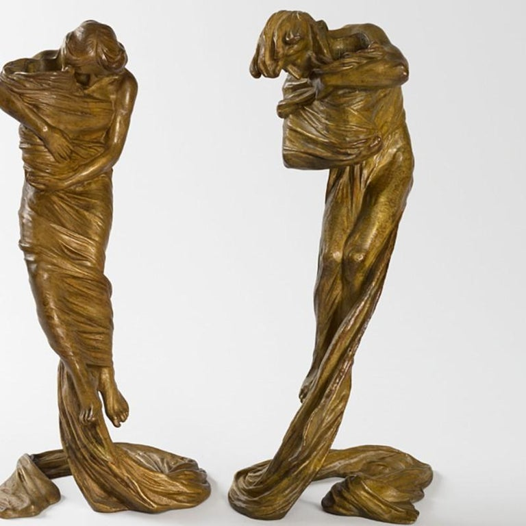 A pair of Austrian Jugendstil gilt bronze figural candlesticks by Gustav Gurschner. The figures bow their heads and are cocooned and suspended in midair by swirling drapery. Their bare arms and shoulders rest atop the multiple folds of the cloth.