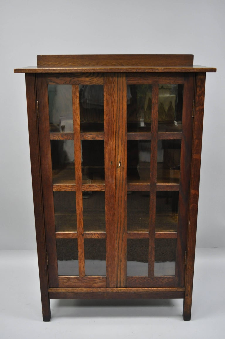 Authentic Gustav Stickley Mission Arts & Crafts oak and glass two-door China cabinet. Item features solid oak wood construction, beautiful wood grain, two swing doors with eight panes of glass each, glass sides with four panes of glass each, total