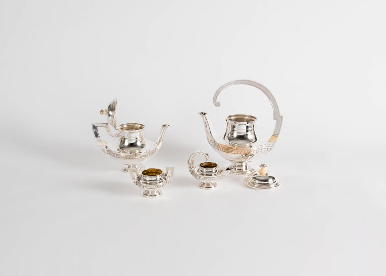 A silver tea set including two tea pots, a creamer, and a sugar bowl, with elegantly arched handles by renowned French silversmith Gustave Keller.