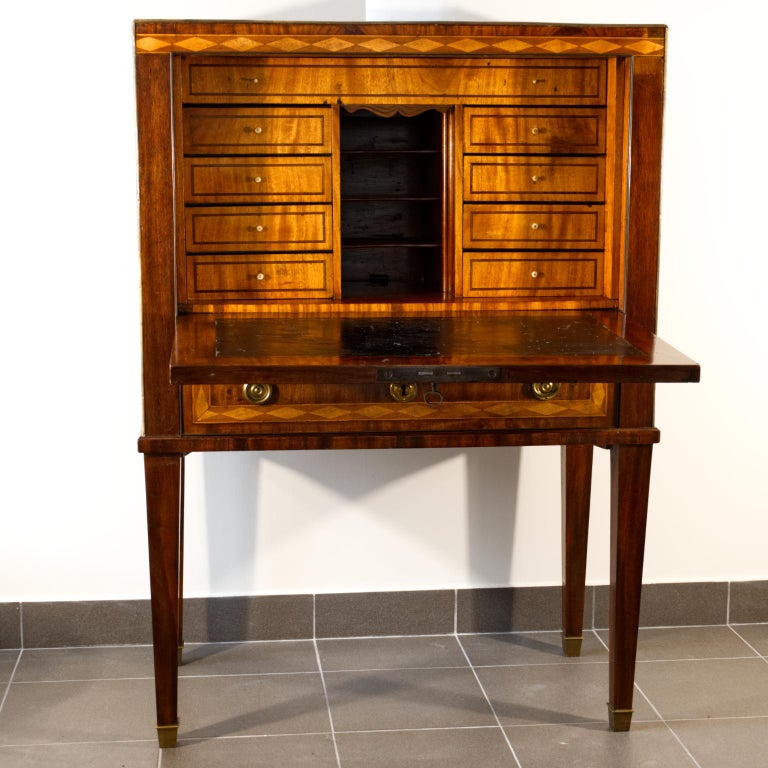 Swedish Gustavian mahogany writing cabinet. The writing part is covered with a black patent leather, with visible traces of use. The inner drawers have bone handles. The upper part is covered with mahogany veneer with brass strips and handles. The