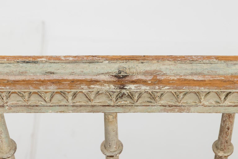 Gustavian style white painted sofa newly upholstered in Swedish fabric, circa 1790s. The piece also features vase turned stiles and carved finials.